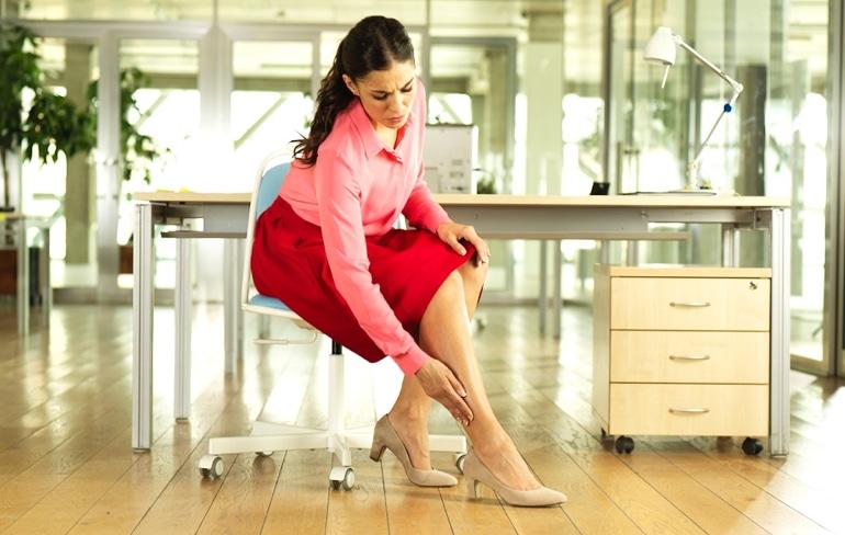 Žena sjedi na uredskom stolcu i dodiruje svoju nogu.