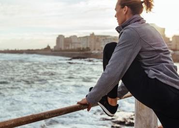 Žena se naginje prema naprijed kako bi istegnula umorne noge nakon trčanja kroz grad, u svrhu prevencije venske insuficijencije