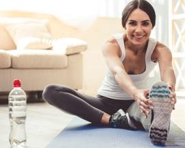 Žena radi vježbe za održavanje zdravlja vena tzv.  vensku gimnastiku na podlošku za jogu kako bi sprječila osjećaj težine u nogama.