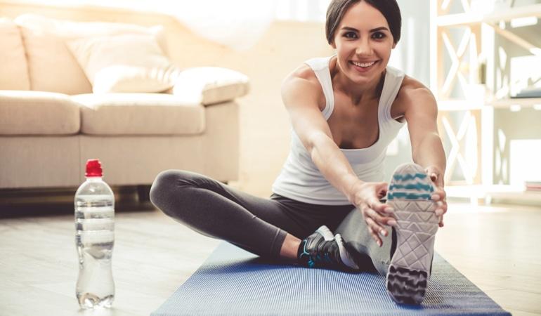 Žena na podlošku za jogu naginje se prema naprijed kako bi istegnula obje noge  i spriječila vensku insuficijenciju.