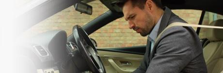 Muškarac s osjećajem težine u nogama sjedi u automobilu